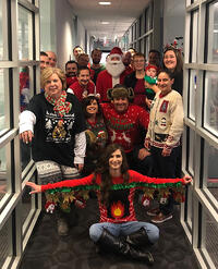 PCI employees pose in Christmas sweaters for a group photo.