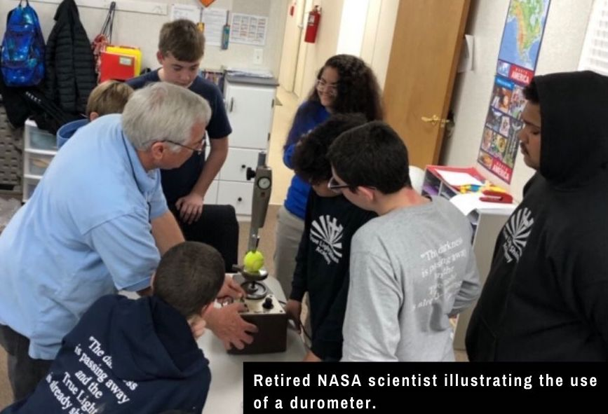 Retired NASA scientist illustrating the use of a dureometer with equipment donated by Syracuse Plastics of North Carolina