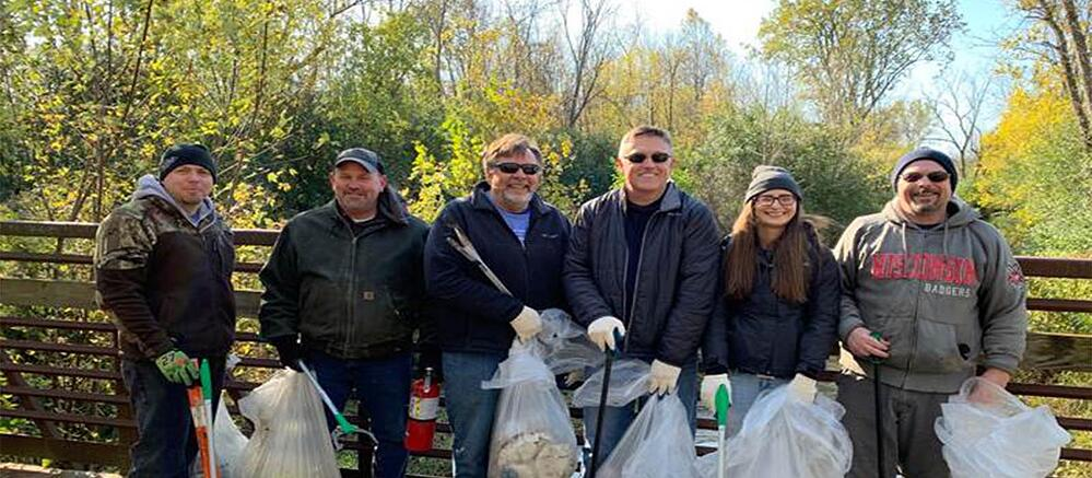 PCI employees hold garbage bags after a river clean up in Menomonee Falls